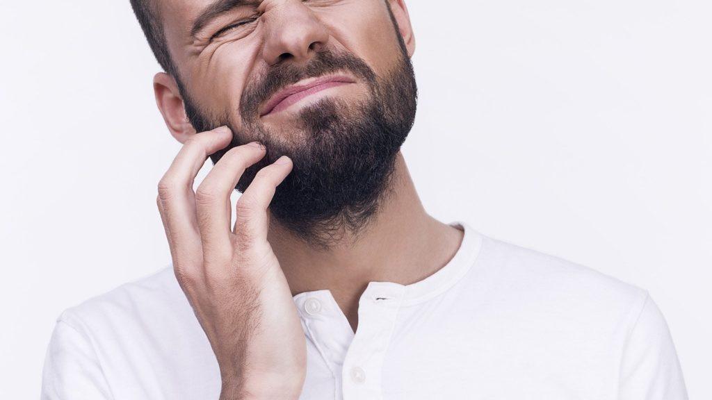 Мужчина чешет бороду
